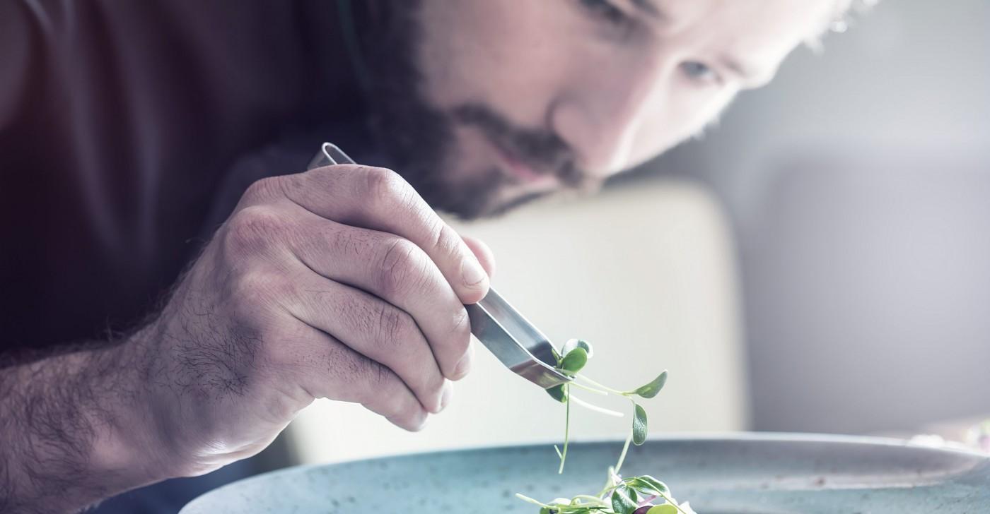 Ein Koch richtet mit der Pinzette Kresse auf einem Teller an